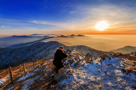 rocky peak: Professional photographer takes photos with camera on tripod on rocky peak at sunset.