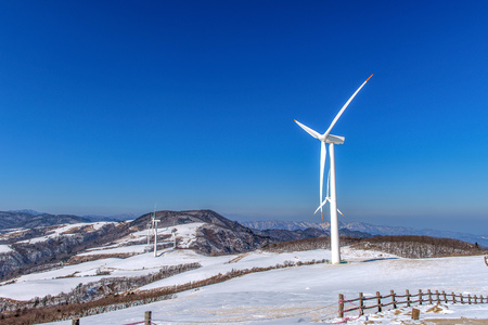 conservation: Wind turbine and blue sky in winter landscape.