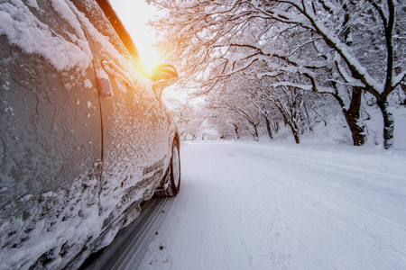 Car and falling snow in winter on forest road with much snow. Stock Photo