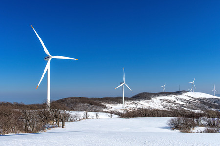 clean energy: Wind turbine and blue sky in winter landscape.