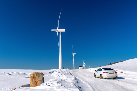 energy fields: Wind turbine and Car with blue sky in winter landscape.