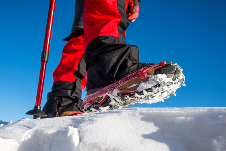 highend: View of walking on snow with Snow shoes and Shoe spikes in winter.