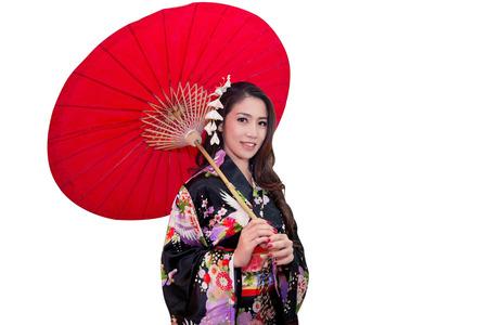Mooie jonge Aziatische vrouw die traditionele Japanse kimono met rode paraplu draagt ??die op witte achtergrond wordt geïsoleerd. Stockfoto