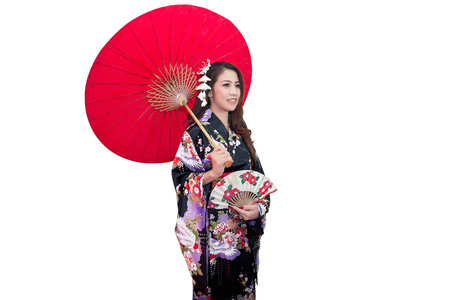 Beautiful young asian woman wearing traditional japanese kimono with red umbrella isolated on white background. Banco de Imagens