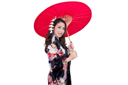 Beautiful young asian woman wearing traditional japanese kimono with red umbrella isolated on white background. Stock Photo