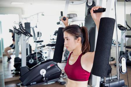 Junge Fitness Frau ausgeführt Übung mit Übungs-Maschine in der Turnhalle.