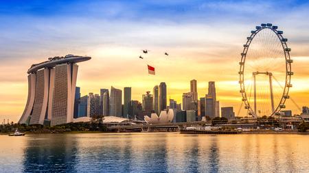 싱가포르 건국 기념일 헬기 도시를 비행하는 싱가포르 플래그를 걸려. 에디토리얼