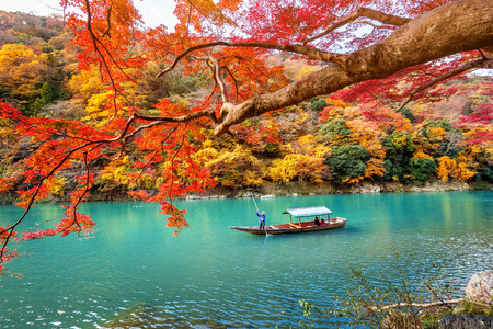 Boatman punting the boat at river. Arashiyama in autumn season along the river in Kyoto, Japan. Archivio Fotografico