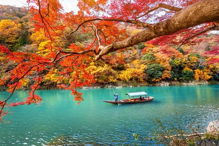 Barquero que patea el barco en el río. Arashiyama en la temporada de otoño a lo largo del río en Kyoto, Japón.