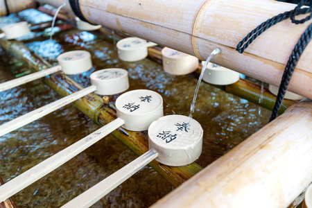 The Shinto Omairi cleansing ceremony by bamboo scoop in Fushimi Inari, Kyoto, Japan