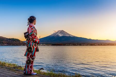 후지산에서 일본 전통 기모노를 입고 아시아 여자. 일본의 카와 구치 호수의 석양.