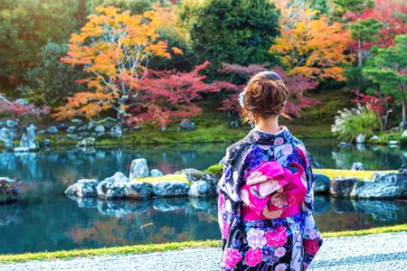 Asian woman wearing japanese traditional kimono in autumn park. Japan Stock Photo