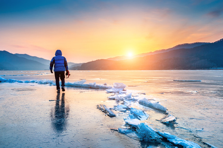 professional photographer with camera on frozen river in winter. South Korea in winter. Stock Photo