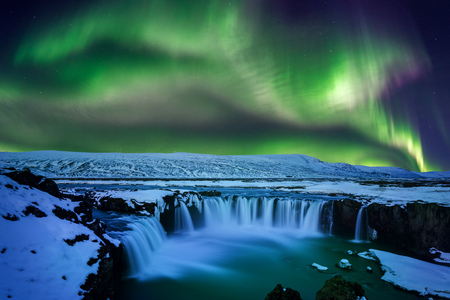 Northern Light, Aurora borealis at Godafoss waterfall in winter, Iceland.
