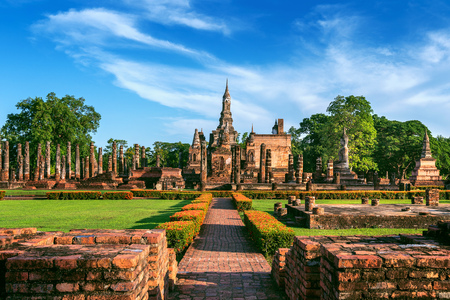 Buddha statue and Wat Mahathat Temple in the precinct of Sukhothai Historical Park, Wat Mahathat Temple