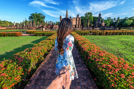 Woman holding mans hand and leading him to Wat Mahathat Temple in the precinct of Sukhothai Historical Park, Wat Mahathat Temple  Thailand.