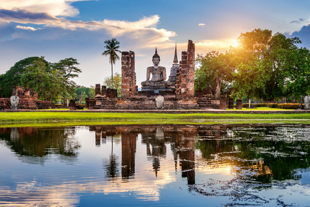 Buddha statue and Wat Mahathat Temple in the precinct of Sukhothai Historical Park,Thailand.