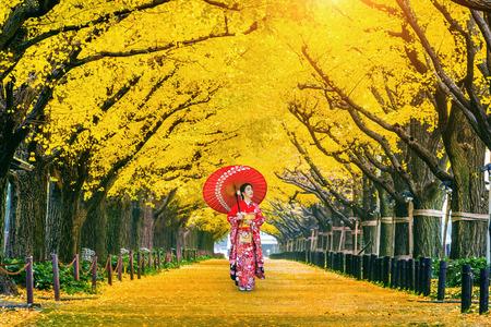 Bella ragazza che indossa il kimono tradizionale giapponese alla fila dell'albero di ginkgo giallo in autunno. Parco d'autunno a Tokyo, Giappone.