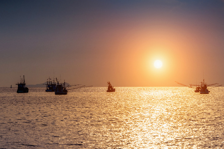 Beautiful sunset at ocean with silhouette of fishing boat. Banque d'images