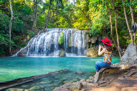Woman sitting at Erawan waterfall in Thailand. Beautiful waterfall with emerald pool in nature. 免版税图像