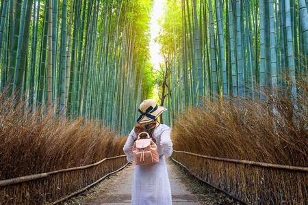 Donna che cammina alla foresta di bambù a Kyoto, Giappone.