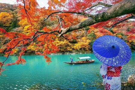 Asian woman wearing japanese traditional kimono at Arashiyama in autumn season along the river in Kyoto, Japan.
