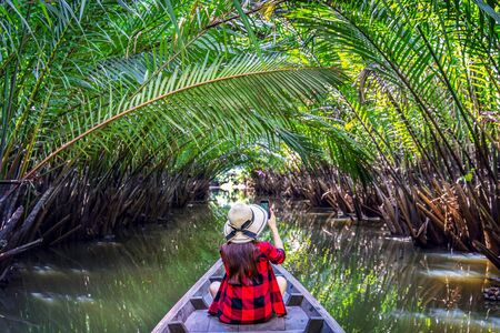 Asian women sitting on a boat at tunnel from nypa fruticans or palm tree in Surat thani,Thailand.