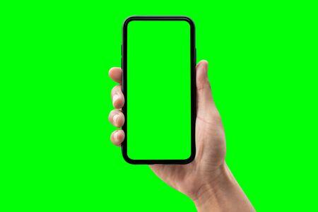 Hand hält Smartphone auf grünem Hintergrund isoliert. Standard-Bild