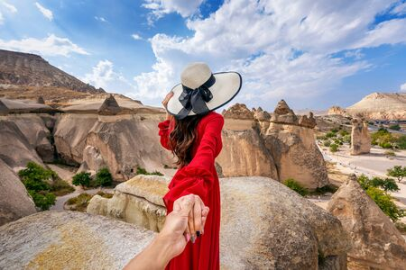 Women tourists holding man's hand and leading him to Fairy Chimneys in Cappadocia, Turkey.