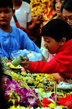 Stock Photo - Chiang Mai,Thailand - Mother holding a baby out of merit in the Buddhist Lent. Editorial