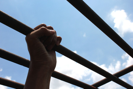 incarcerated: Hand of the prisoner on a steel lattice close up (jail, prison, man)