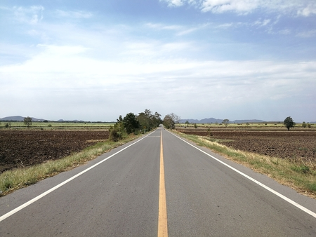 as far as the eye can see: wide open prairie with a paved highway stretching out as far as the eye can see with beautiful under a bright blue sky in the summer time.
