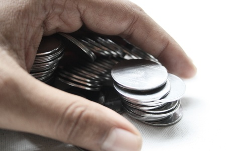 A hand covering some coins. photo