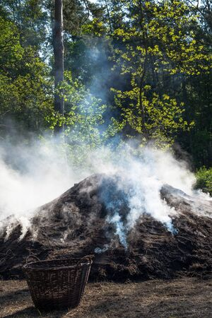 The constant treatment of the pile fire protects the success of the charcoal production. Фото со стока