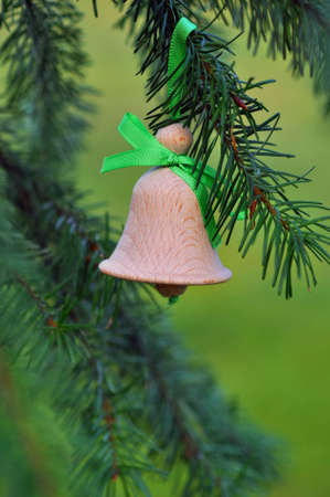 Traditional old czech christmas decoration, small bell from wood with green ribbon Stock Photo - 11588668
