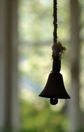Metal bell hanging on a string against bright green-yellow background and window Stock Photo