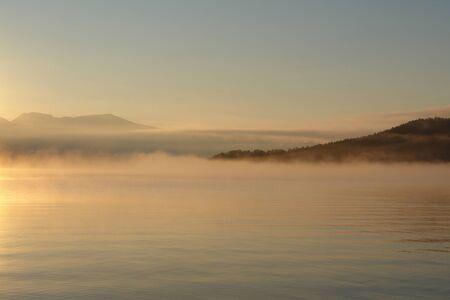 A scenic view - morning fog over the calm water of Chivyrkuisky Bay. Golden sunrise in Snake / Zmeyevaya Bay, peninsula Svyatoy Nos ( Imagens