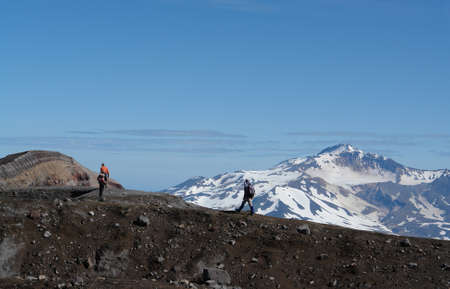 The tourists are walking along a trail, passing on one of the walls of the crater of Gorely volcano (Mutnovsky volcano is visible on the background), Kamchatka Peninsula, Far East Russia 版權商用圖片