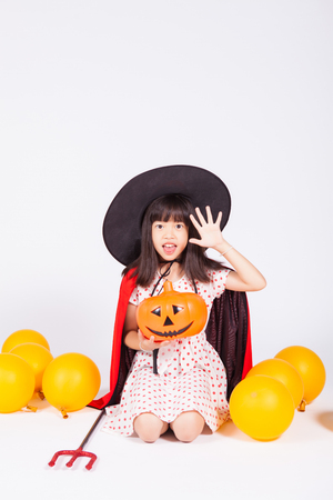 little girl in black hat  with halloween pumpkin
