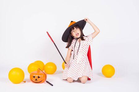 little girl in black hat  with halloween pumpkin