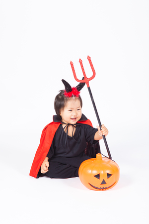 devil girl in black suit and red cape  with halloween pumpkin and trident Archivio Fotografico