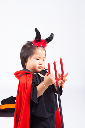 devil girl in black suit and red cape  with halloween pumpkin and trident Stock Photo
