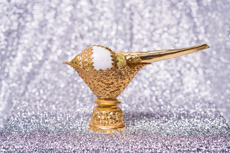 Conch shell on golden tray for blessed water in Thai wedding ceremony on bokeh background