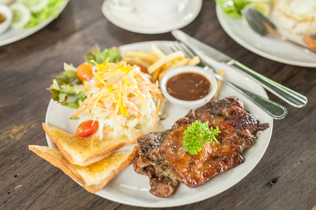 Grilled beef steak served with French fries and vegetables on a white plate