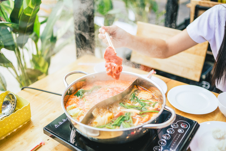 chopsticks take beef slice into shabu shabu pot, healthy food Standard-Bild