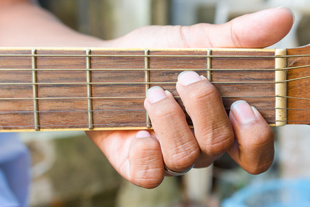 chords: Musicians hand playing acoustic guitar. Am chords Stock Photo