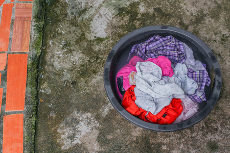 Soak dirty clothes in the basin black for cleanse,Thailand washing clothes style ancient and soak with detergent in the evening. Stock Photo