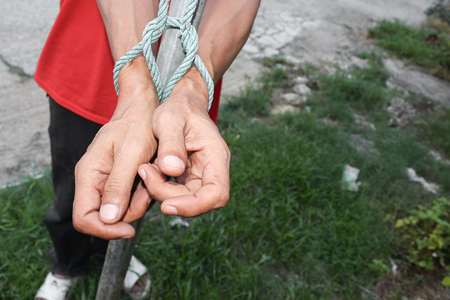 Hands tied up with rope, male with post steel hands tied  rope : select focus front  hands and soft-focus background :