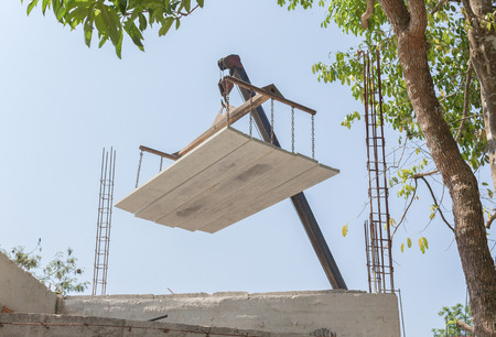 maneuverable: Industrial Crane operating works loading of cement sheet In construction.