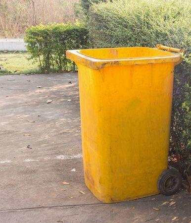 dispose: yellow dustbins trashcan rubbish bins in the garden. Stock Photo